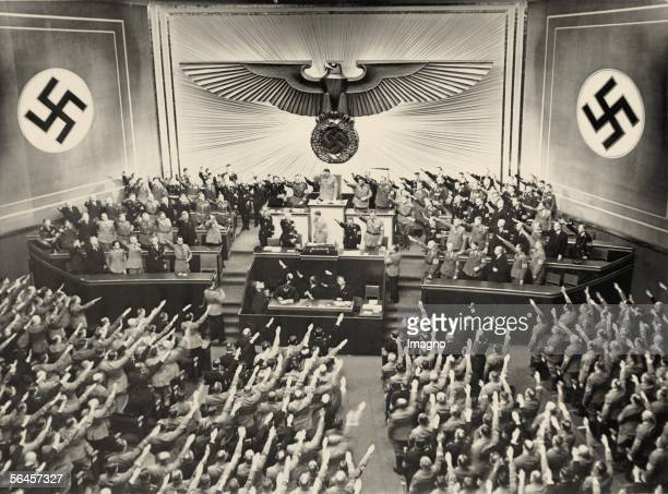 Adolf Hitler in the german Reichstag After a speech the audience gives him standing ovations Behind Hitler is Reichspraesident Hermann Goering...