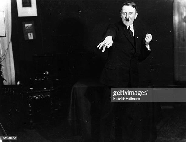Adolf Hitler leader of the National Socialist German Workers' Party strikes a pose for photographer Heinrich Hoffmann whilst listening to a recording...