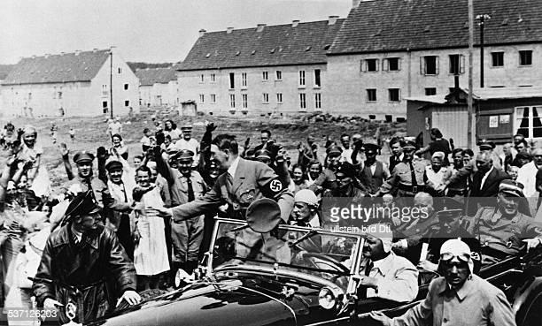 Adolf Hitler Politiker NSDAP D auf der Fahrt durch eine Neubausiedlung in Braunschweig von den Bewohnern mit Jubel begrüsst am Steuer des Wagens...