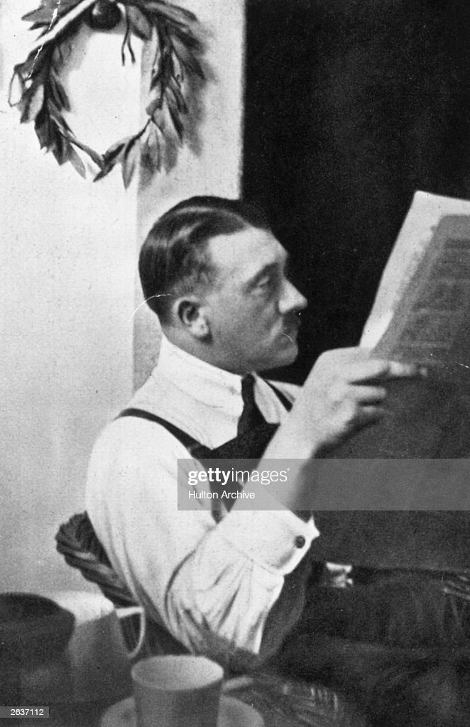 Adolf Hitler sits reading a paper during his imprisonment in Landsberg Jail after the failure of the Munich Putsch A laurel wreath hangs on the wall