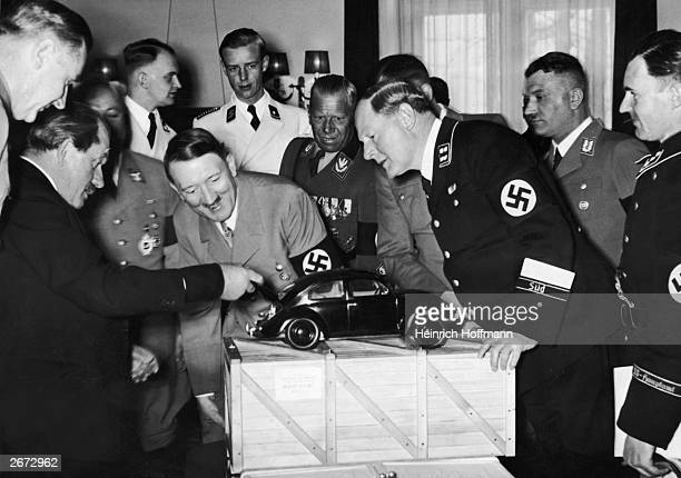 Adolf Hitler the German Dictator admires a model of the Volkswagen car and is amused to find the engine in the boot He is with the designer Ferdinand...