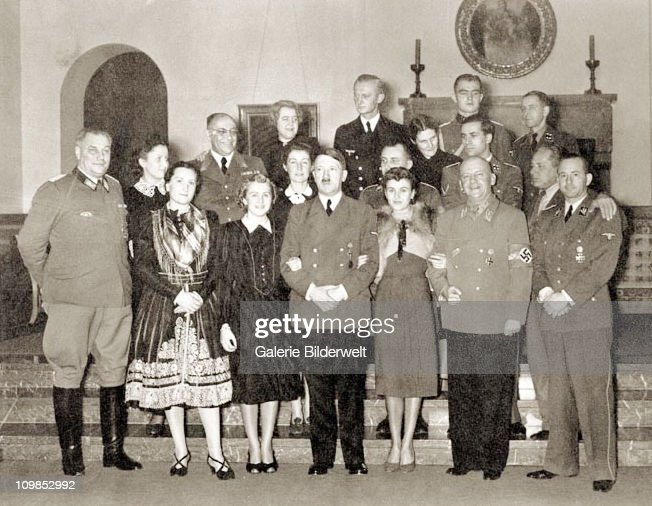 Adolf Hitler (1889 - 1945) with guests at at his residence, the Berghof near Berchtesgaden, Germany, 31st December 1939. Front row left to right: Wilhelm Bruckner (Hitler's Chief Adjudant), Christa Schroder (Hitler's secretary), Eva Braun, Adolf Hitler, Gretl Braun (Eva's sister), Adolf Wagner (Gauleiter of Munich) and Otto Dietrich (press chief). Second row, left to right: Gerda Daranowski (Hitler's Secretary), Margarete Speer, Martin Bormann, Dr. Karl Brandt and Heinrich Hoffmann. Back row, left to right: Dr. Theo Morell (Hitler's personal physician), Hannelore Morell, Karl-Jesko von Puttkamer (Hitler's naval adjudant), Gerda Bormann, Max Wunsche (one of Hitler's SS aides) and Heinrich Heim (from Bormann's staff).