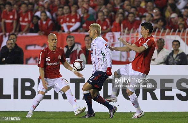 Adolfo Bautista of Mexico's Chivas vies for the ball with Nei and Bolivar of Brazilian Internacional during their Libertadores Cup final match at...