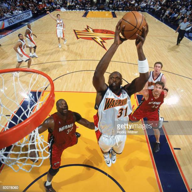 Adonal Foyle of the Golden State Warriors grabs a rebound in front of Shaquille O'Neal of the Miami Heat during a game at The Arena in Oakland on...