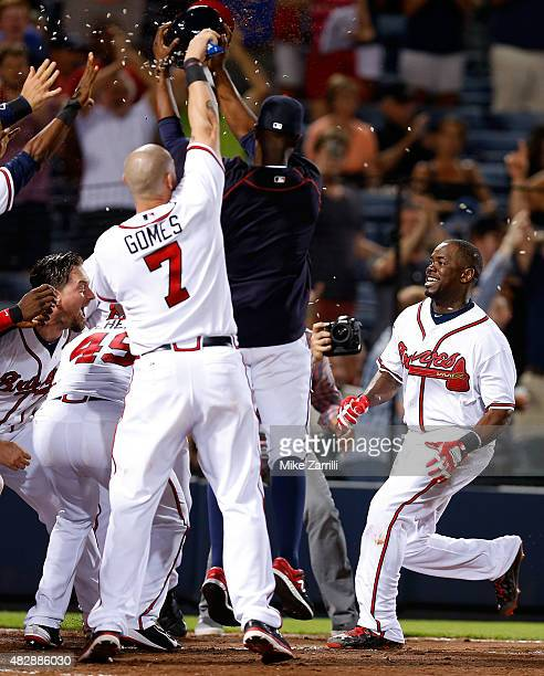 Adonis Garcia of the Atlanta Braves is mobbed by teammates at home plate after hitting a gamewinning tworun home run in the 12th inning during the...
