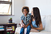 Happy latin mother embracing her adopted son on couch and smiling. Cheerful woman playing with her african child at home. Portrait of son and mom having fun together after school.