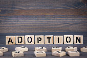Adoption word written on wood block. Dark wood background with texture.