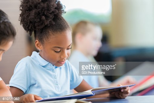 Adorable African American girl reading books in the school library : Stock Photo