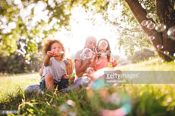 Adorable famille afro-américaine à eachother souffle des bulles de savon