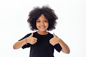 Adorable and cheerful African American kid with afro hairstyle giving thumbs up isolated over white background
