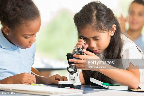 Adorable Asian girl uses microscope to study something