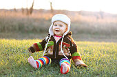 An adorable 8 month old baby girl with bright blue eyes is laughing while bundled up in a winter hat and knit sweater on a cold fall day.