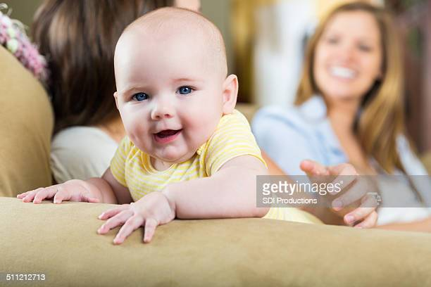 Adorable baby smiling while mother talks to friend