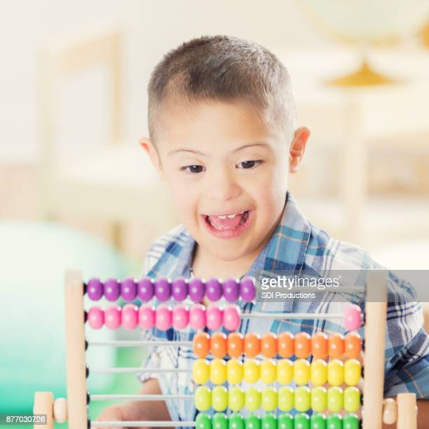 Adorable boy enjoys playing with an abacus at school