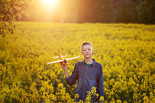 Cute Boy holds toy plane in his hand on sunset in summer day.