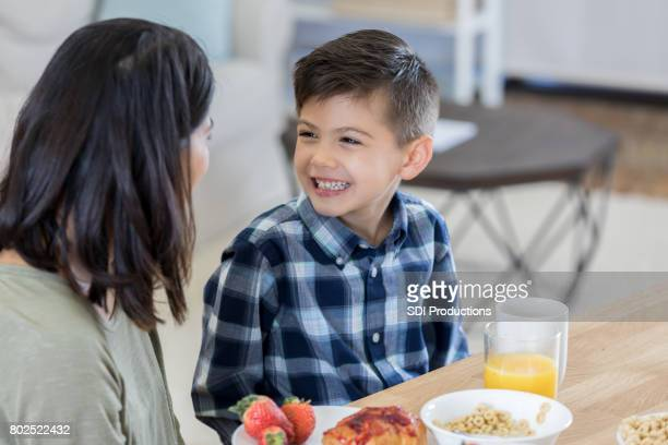 Adorable boy smiles at his mom during breakfast