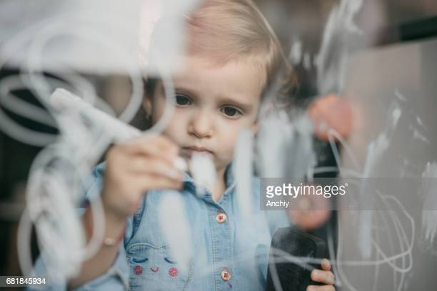 Adorable child draws objects on the window