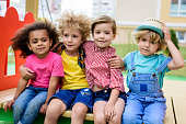 adorable curly boy embracing two multicultural children while other boy sitting near at playground
