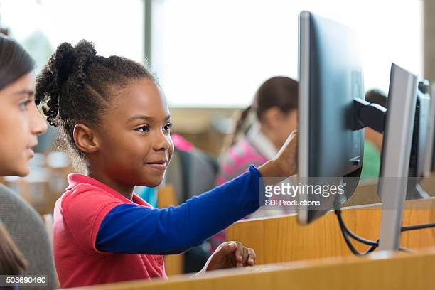 Adorable elementary age girls using computers in school library