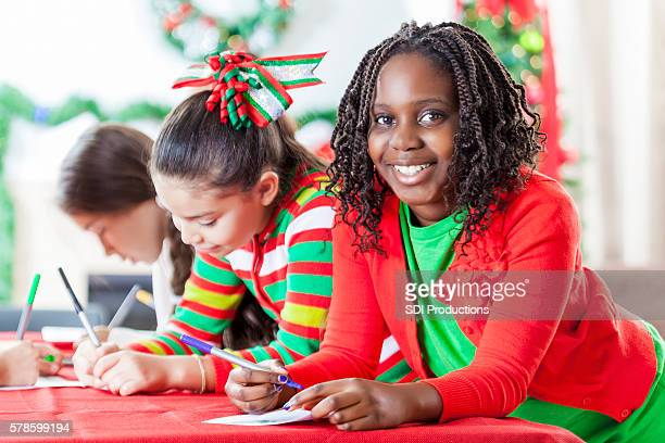Adorable girl and friends work on Christmas charity project