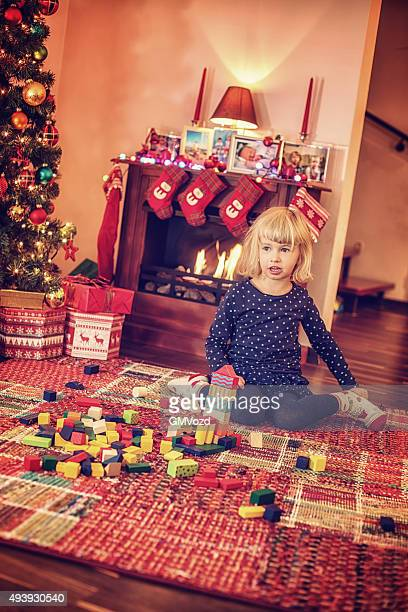 Adorable Girl Playing in in front of Christmas Tree