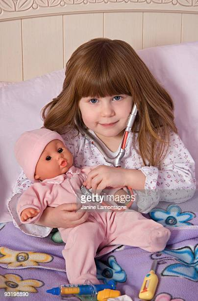 Adorable girl sick in bed with her doll