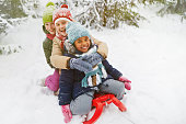 Three multi-ethnic girls on sledge having fun in snow