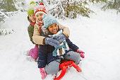 Three multi-ethnic girls on sledge having fun in snow