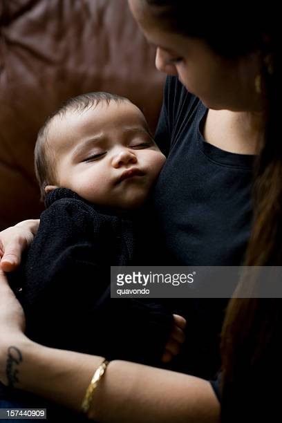 Adorable Hispanic Baby Boy Sleeping in Arms of Mother