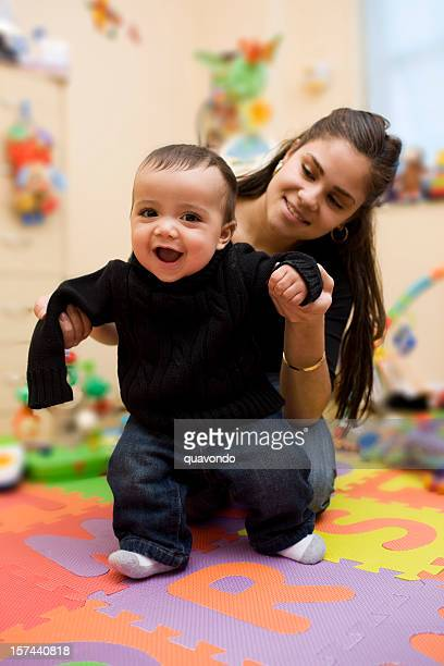 Adorable Hispanic Baby Taking First Steps with Mother in Playroom