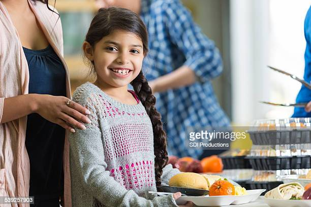 Adorable Hispanic girl holding tray of food at food bank