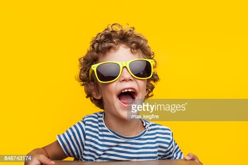 Adorable niño en gafas de sol brillantes naranja : Foto de stock