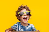 Portrait of cheerful little boy wearing adult sunglasses and looking away on orange background.