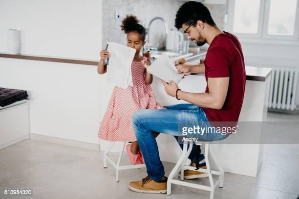 Liebenswert Kind versucht zu imitieren ihres Vaters durch Zeitungen wie er halten