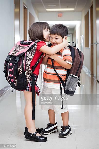 Adorables enfants Whispering avec sacs à dos dans le couloir de l'école élémentaire
