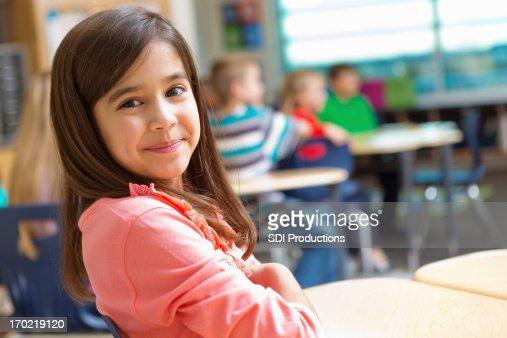 Adorable kindergarten or elementary school girl at desk in classroom