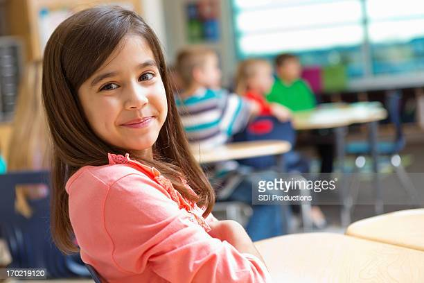 Adorable kindergarten or elementary school girl at desk in classroom
