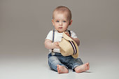 Cute baby boy posing in jeans. Adorable little child in studio.