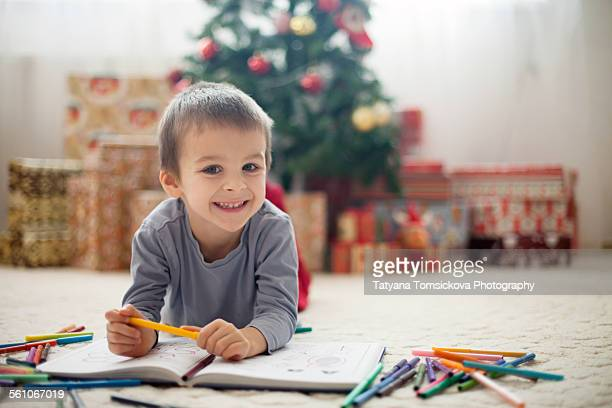Adorable little boy, coloring in a book