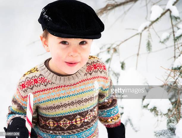 Adorable Little Boy Eating Giant Candy Cane Outside in Snow