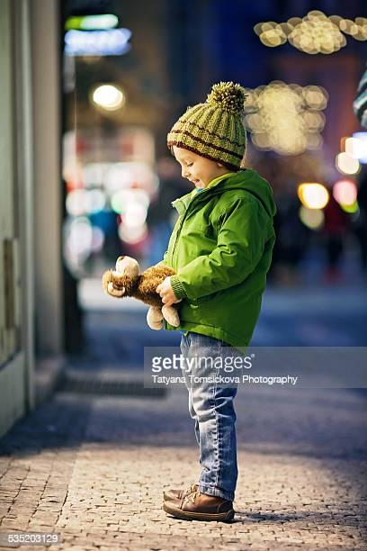 Adorable little boy, holdine a monkey