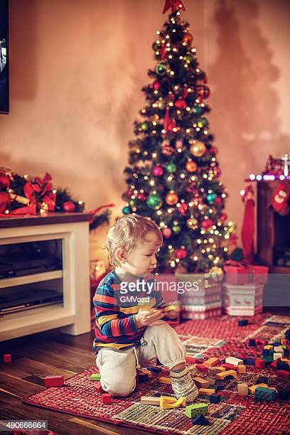 Adorable Little Boy Playing in in front of Christmas Tree