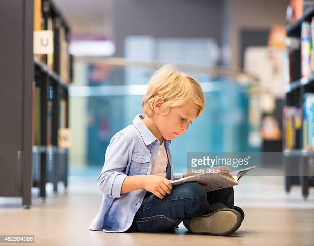 Adorável Little Boy sentado na biblioteca
