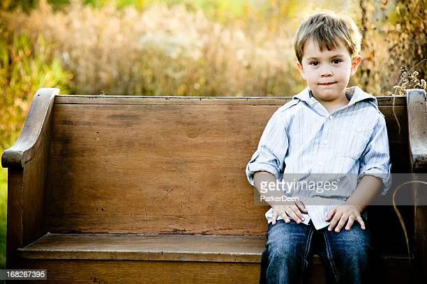 Adorable Little Boy Sitting on Wooden Antique Bench in Prairie