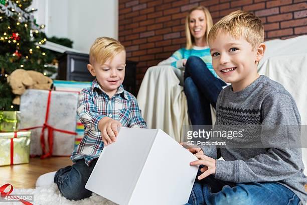 Encantadores niños que regalos de Navidad mientras mamá relojes