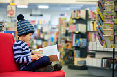 Adorable little child, boy, sitting in a book store, reading books