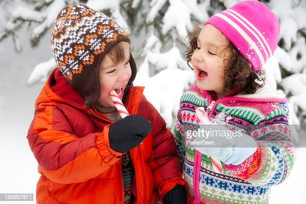 Adorable Little Girl and Boy Playing Laughing in Snow Together