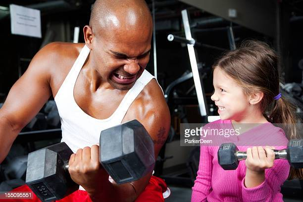 Adorable Little Girl and Handsome Athletic Man Lifting Weights