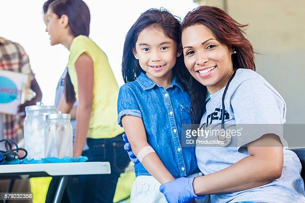 Adorable little girl being held by a volunteering nurse