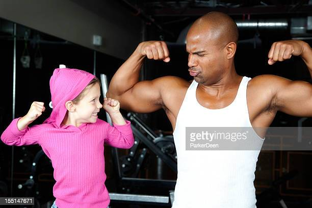 Adorable little girl comparing muscles to athletic man